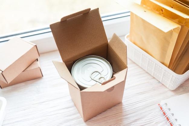 Het blik van het voedseltin dat in kartondoos wordt verpakt, het concept van de voedsellevering