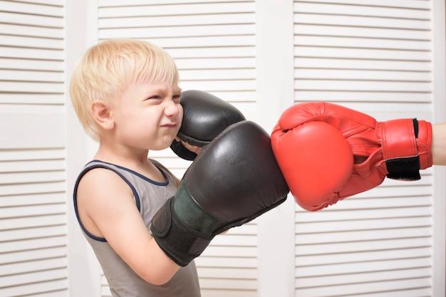 Het blonde jongen in dozen doen met dient rode handschoen in. emoties