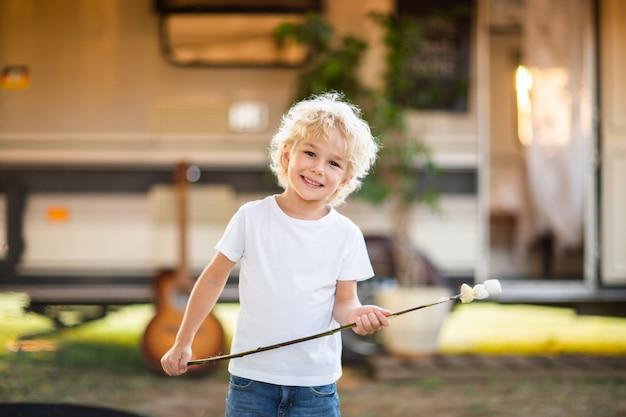 Het blonde jongen stellen met heemst bij familie het kamperen