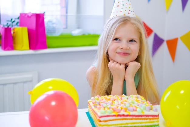 Het blonde kaukasische meisje zit zorgvuldig en dromerig aan feestelijke lijst dichtbij de cake van de verjaardagsregenboog en doet een wens. kleurrijke achtergrond met ballonnen