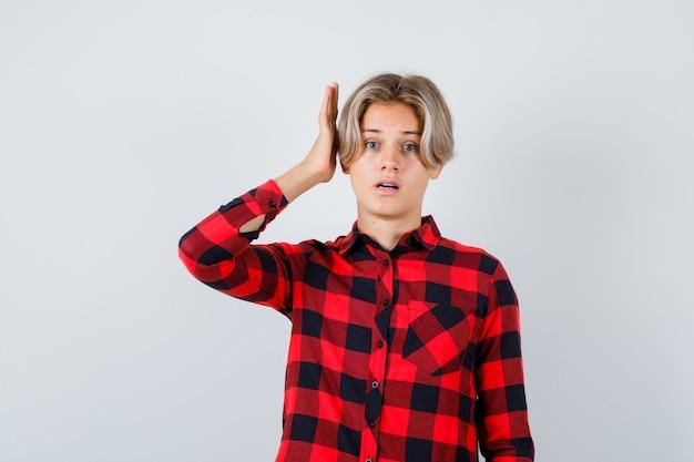 Het blonde mannetje van de tiener met hand dichtbij oor in toevallig overhemd en peinzend kijkend. vooraanzicht.