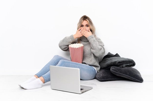 Het blonde meisje dat van de tiener popcorn eet terwijl het letten van op een film op laptop die mond behandelen met handen