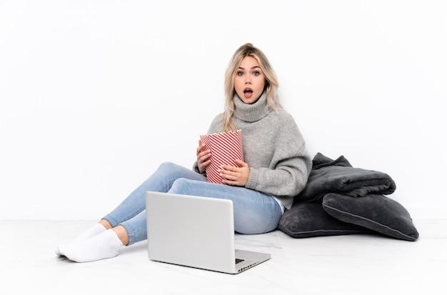 Het blonde meisje dat van de tiener popcorn eet terwijl het letten van op een film op laptop met verrassingsgelaatsuitdrukking