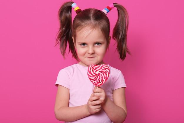 Het blonde meisje staat recht, heeft een kleurrijke lolly in handen, heeft een fronsend gezicht en heeft geen zin om snoep met iemand te delen. ruimte voor reclame kopiëren.