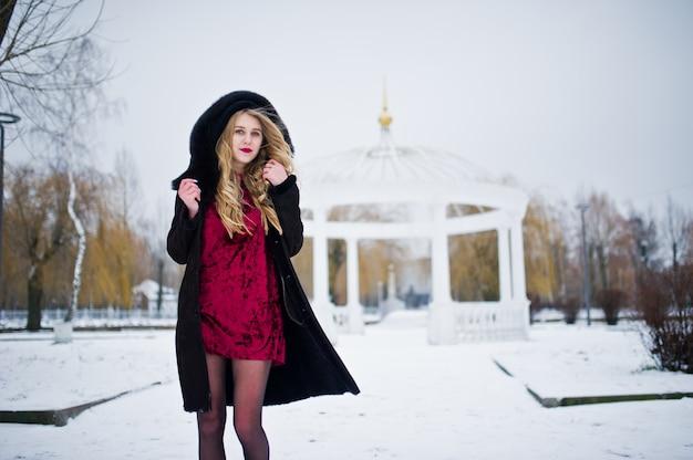 Het blonde meisje van de elegantie in bontjas en het rode avondjurk stellen bij de winter sneeuwdag.