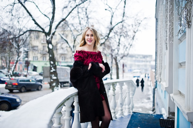 Het blonde meisje van de elegantie in rode avondjurk en bontjas bij straten van stad in de winterdag.