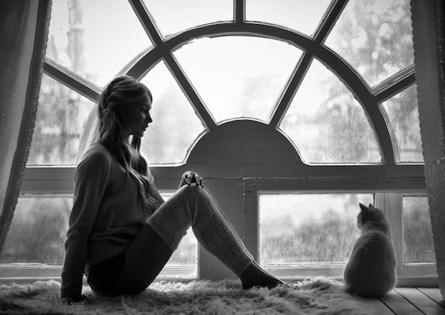 Het blonde meisje van de kunstfoto en het witte venster van de kattenzitting
