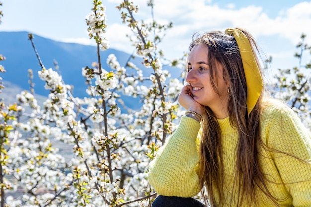 Het blonde vrouw stellen op een achtergrond van de kersenbloesem. jerte vallei. extremadura, spanje.