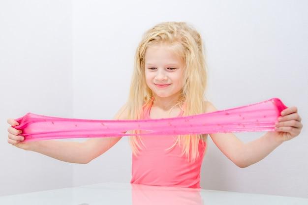 Het blondemeisje die roze uitrekken schittert slijm