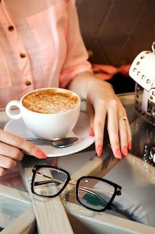 Het blondemeisje drinkt koffie in koffiewinkel, glazen, handtas. blogger plat lag. ochtendkoffie in café. advertentieglazen, optiekwinkel.