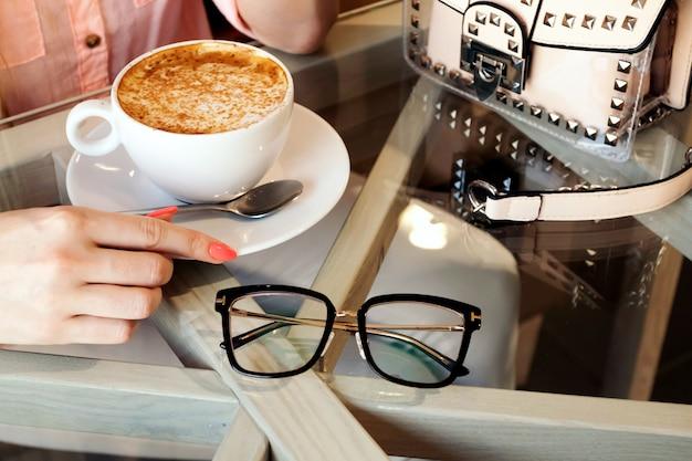 Het blondemeisje drinkt koffie in koffiewinkel, glazen, handtas. blogger plat lag. ochtendkoffie in café.