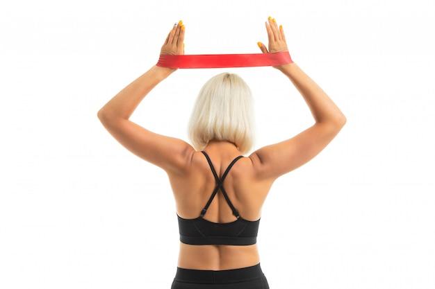 Het blondemeisje gaat binnen voor sporten met een zwarte sporten eenvormig op wit