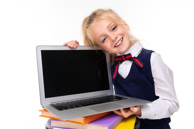 Het blondemeisje houdt laptop met model op witte muur