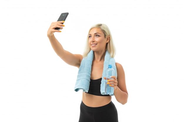 Het blondemeisje in een sporten uniform met een handdoek maakt selfie op wit