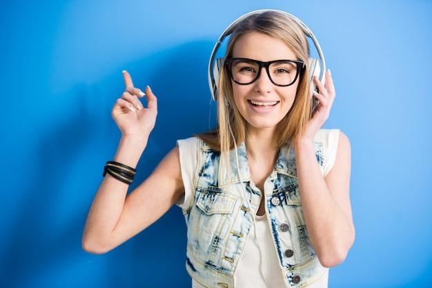 Het blondemeisje luistert een muziek met hoofdtelefoon.