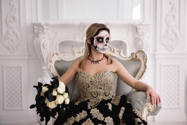 Het blondemeisje met suikerschedel maakt. day of dead of halloween