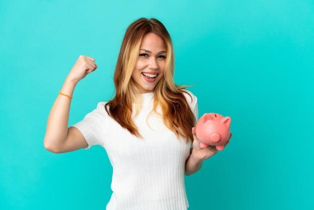 Het blondemeisje van de tiener houdt een spaarpot over geïsoleerde blauwe achtergrond die een overwinning viert