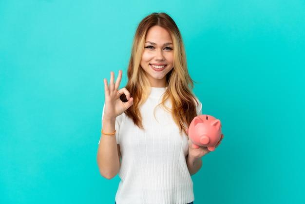 Het blondemeisje van de tiener houdt een spaarpot over geïsoleerde blauwe achtergrond die ok teken met twee handen toont Premium Foto