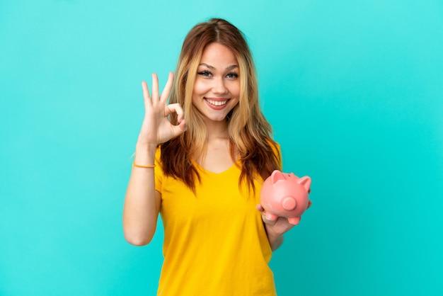 Het blondemeisje van de tiener houdt een spaarpot over geïsoleerde blauwe achtergrond die ok teken met vingers toont