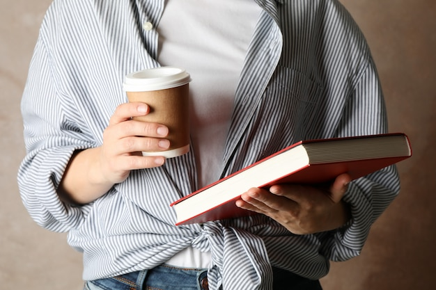 Het boek en de koffie van de vrouwenholding tegen bruine achtergrond, vooraanzicht