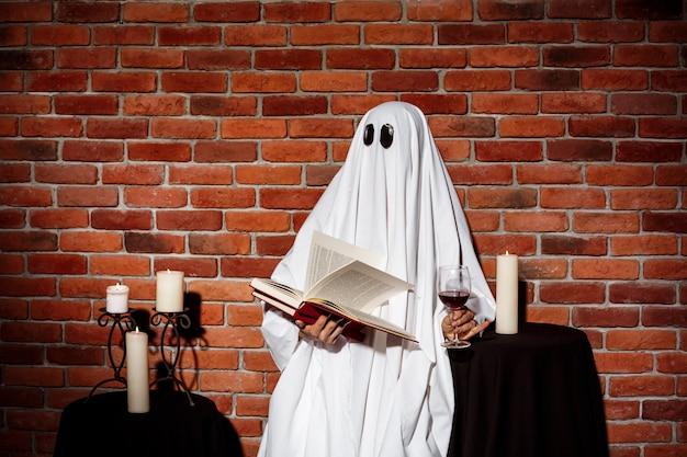 Het boek en de wijn van de spookholding over bakstenen muur. halloween feest.