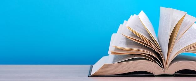 Het boek ligt open, ligt op tafel, de bladen waaieren uit op een blauwe achtergrond.