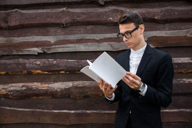 Het boek van de jongenslezing op houten backround wordt geïsoleerd die