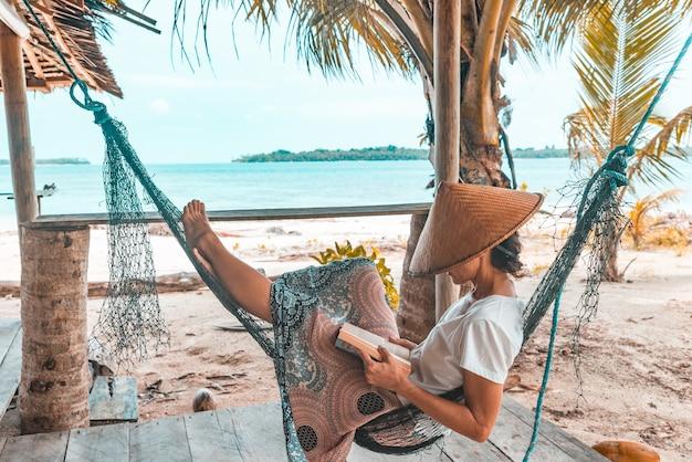 Het boek van de vrouwenlezing op hangmat tropisch strand, echte mensen