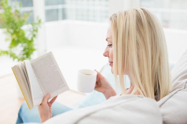 Het boek van de vrouwenlezing terwijl het hebben van koffie op bank