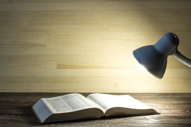 Het boek wordt verlicht door licht van een lamp op een tafel in een donkere kamer