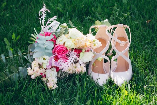Het boeket en de schoenen van de bruid op het gras