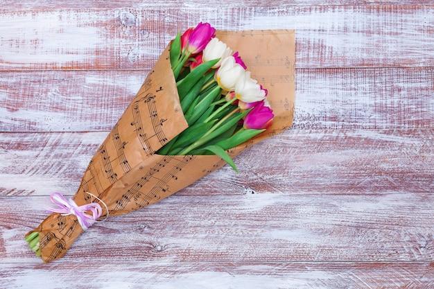 Het boeket tulpen is verpakt in papier dat op een houten achtergrond is geïsoleerd