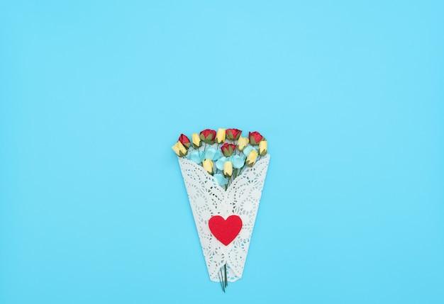 Het boeket van ambachtelijke bloemen verpakt in een witte kanten bundel op blauwe achtergrond