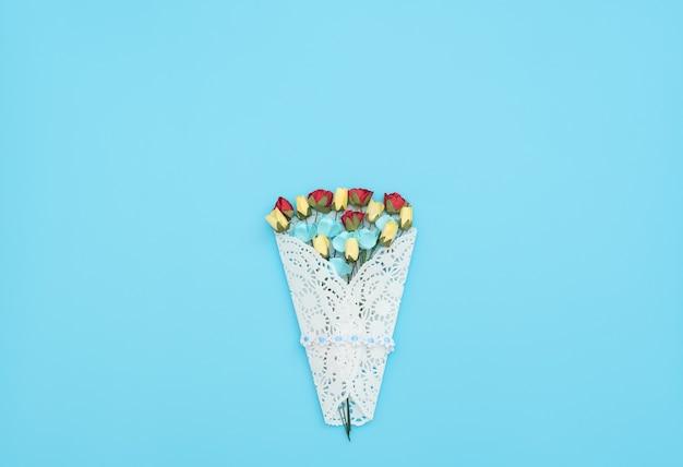 Het boeket van ambachtelijke bloemen verpakt in een witte kanten bundel op blauwe achtergrond.