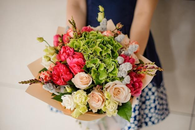 Het boeket van de meisjesholding van bloemen in handen