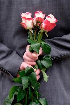Het boeket van de mensenholding van rozen achter rug