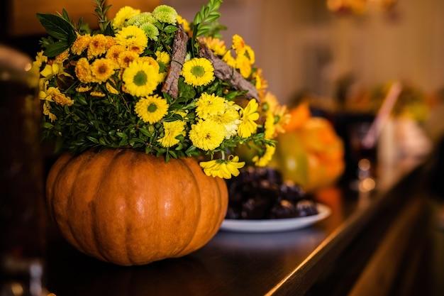 Het boeket van herfstbloemen in de pompoen op de viering van halloween.
