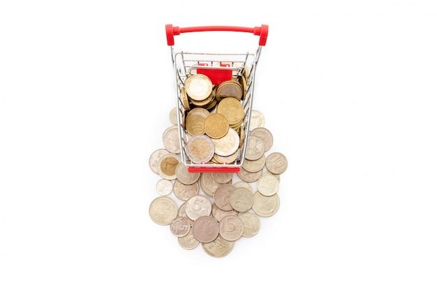 Het boodschappenwagentje met euro muntstukken daarin berijdt omhoog een stapel van oude en roestige russische muntstukken op witte achtergrond. vrije ruimte voor tekst.