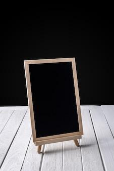 Het bord op houten vloer en zwarte achtergrond