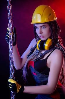 Het bouwmeisje met een helm en een overall met een lange ketting in haar handen