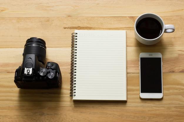 Het bovenaanzicht van de fotograaf, een houten tafel met een camera, notebook, koffie en smartphone.