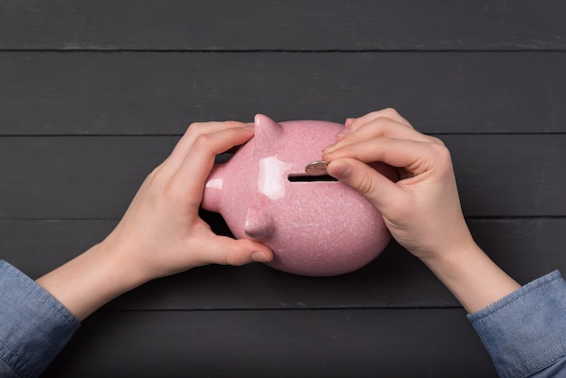 Het bovenaanzicht van de handen van het kind brengt spaarvarkenmuntstuk aan. geld besparen concept