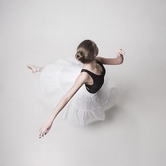Het bovenaanzicht van de tiener ballerina op witte ruimte