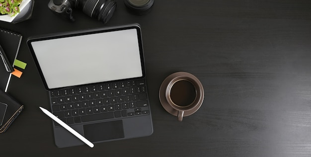 Het bovenaanzicht van een zwarte tafel wordt omringd door een computertablet en fotograafapparatuur.