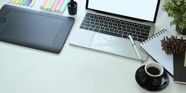 Het bovenaanzicht van het witte bureau wordt omgeven door een computerlaptop en apparatuur van een grafische ontwerper.