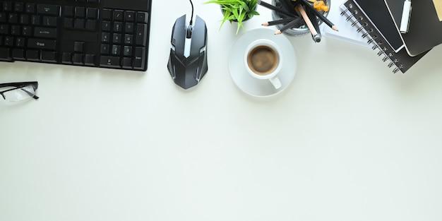 Het bovenaanzicht van het witte bureau wordt omgeven door een koffiekopje en kantoorapparatuur.