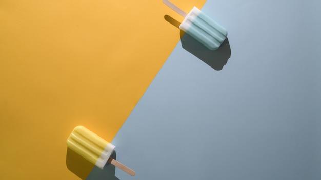 Het bovenaanzicht van ijslollys van het limoen en de blauwe frambozensmaak en exemplaarruimte op vlakte leggen gele en blauwe achtergrond