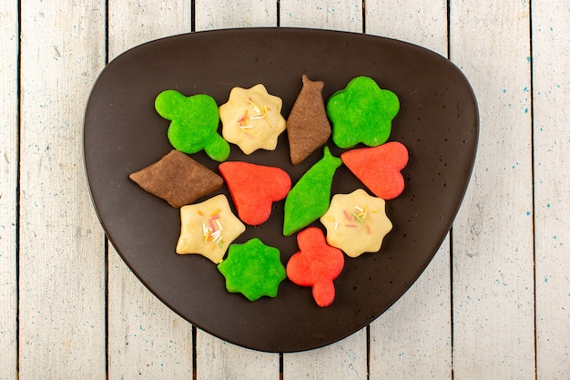 Het bovenaanzicht van kleurrijke heerlijke koekjes vormde veelkleurige veelkleurige binnen donkere plaat