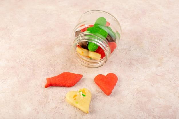 Het bovenaanzicht van kleurrijke heerlijke verschillende koekjes gevormd binnen kan op het roze oppervlak