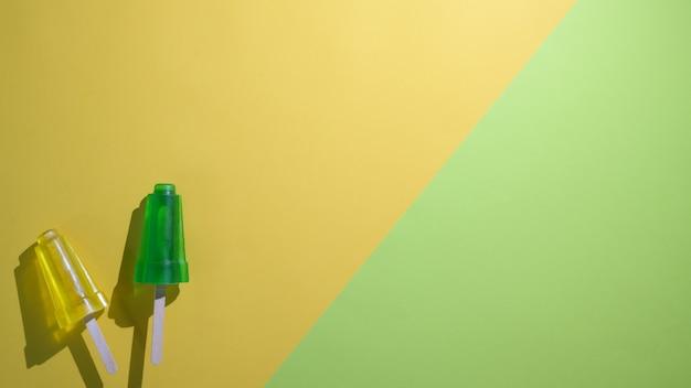 Het bovenaanzicht van limoen en citroensmaakijslollys en exemplaarruimte op vlakte legt gele en groene achtergrond